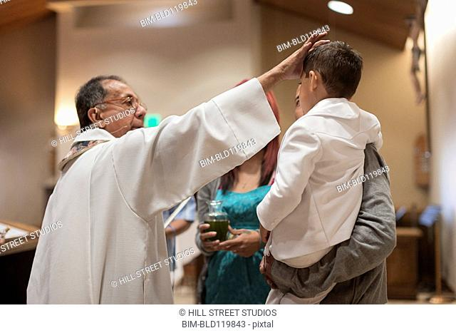Priest anointing boy in church