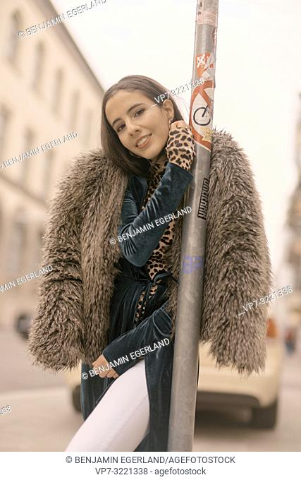 coy woman leaning on lamppost at street in city, Munich, Germany