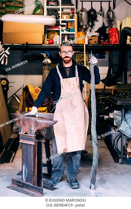 Portrait of metalworker leaning on anvil in forge workshop