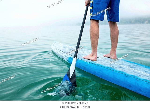 Legs of young man stand up paddleboarding on lake Pilsensee, Germany