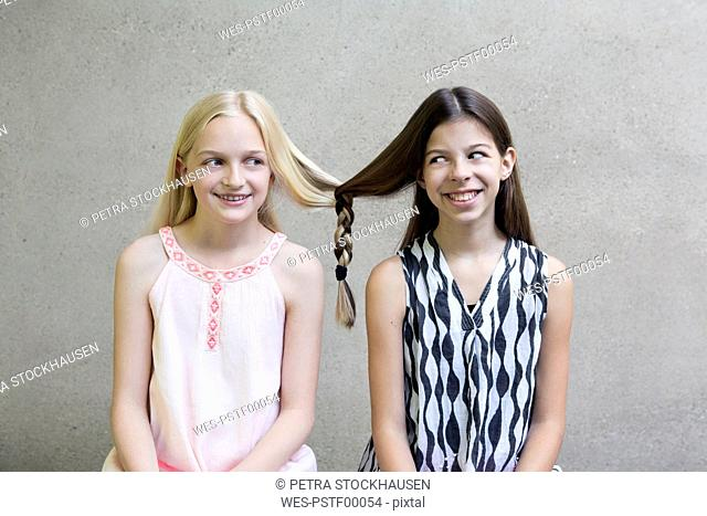 Portrait of two long-haired girls with one braid
