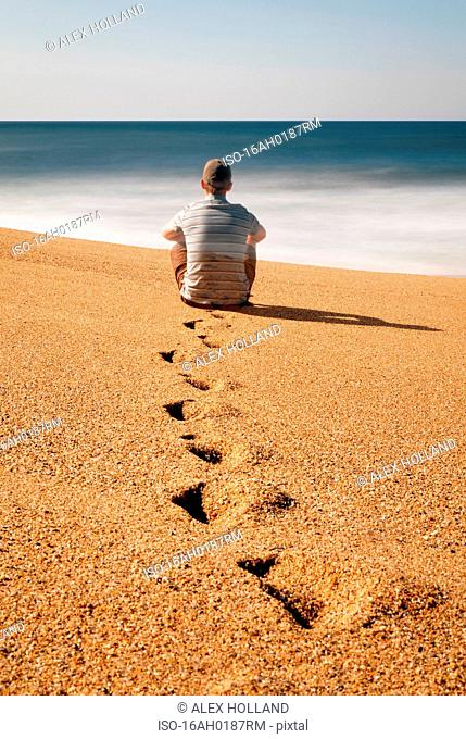 Man sitting on beach, looking out to sea