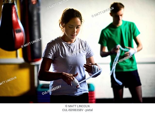 Young male and female boxers wrapping hands in bandages