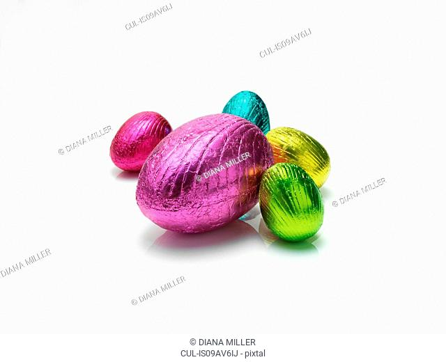 Colourful easter eggs in shiny foil on white background