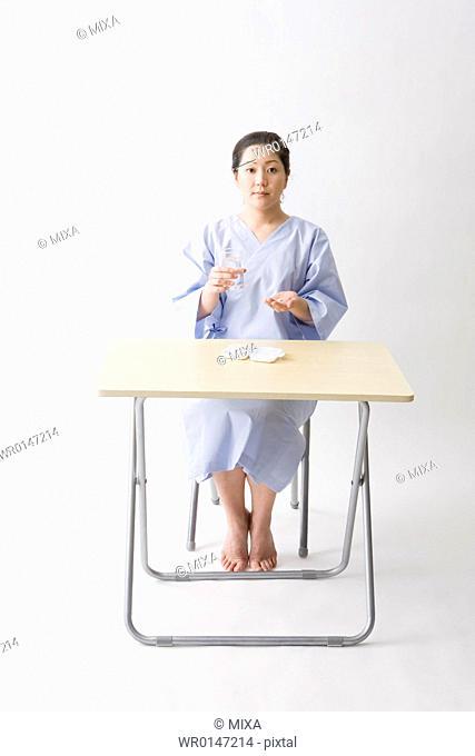 Mid adult woman taking pills