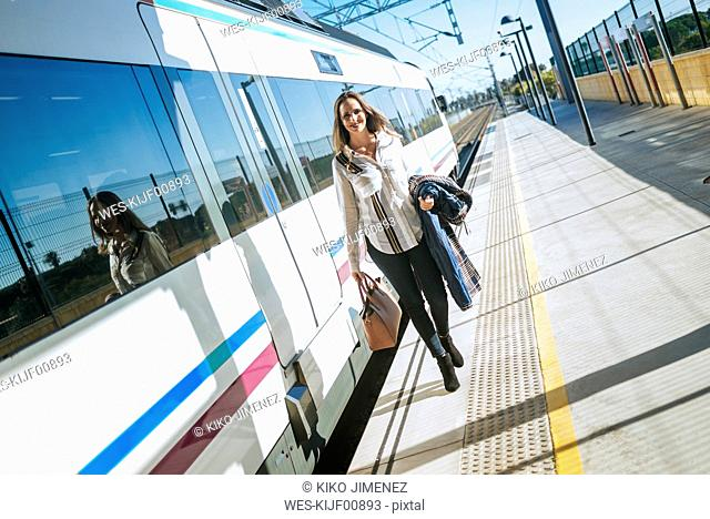 Woman walking on platform next to train