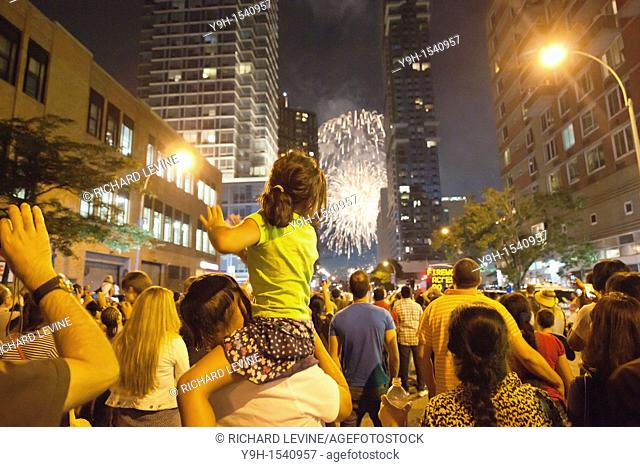 Thousands of spectators line the streets on the west side of Manhattan in New York to view the Macy's Fourth of July fireworks display above the Hudson River