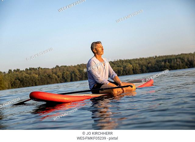Mature man sitting on paddleboard on a lake by sunset relaxing