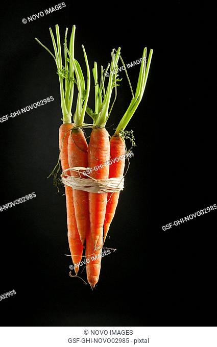 Bunch of Carrots Tied Together by Raffia Ribbon Against Black Background
