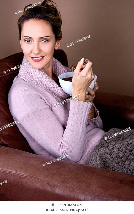 A mid adult woman eating a bowl of cereal