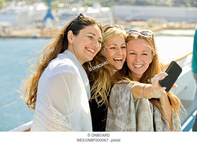 Three happy women taking a selfie on a cruise ship