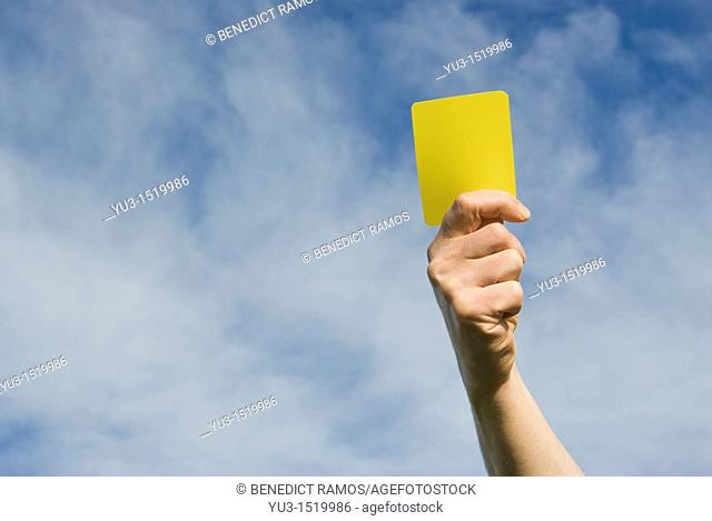 Hand of referee waving a yellow card