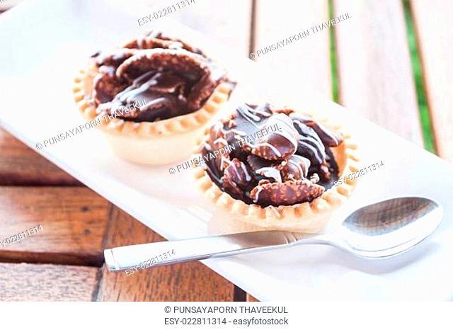 Crispy chocolate tarts on white plate