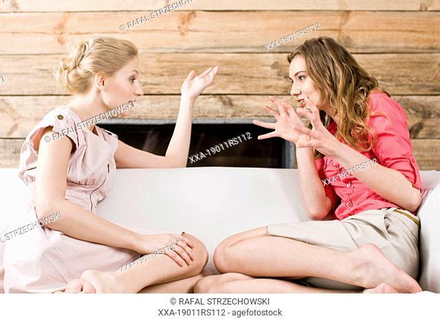 Women gossiping on sofa