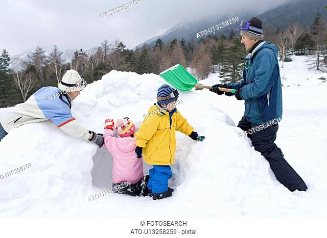 Family making snow cave