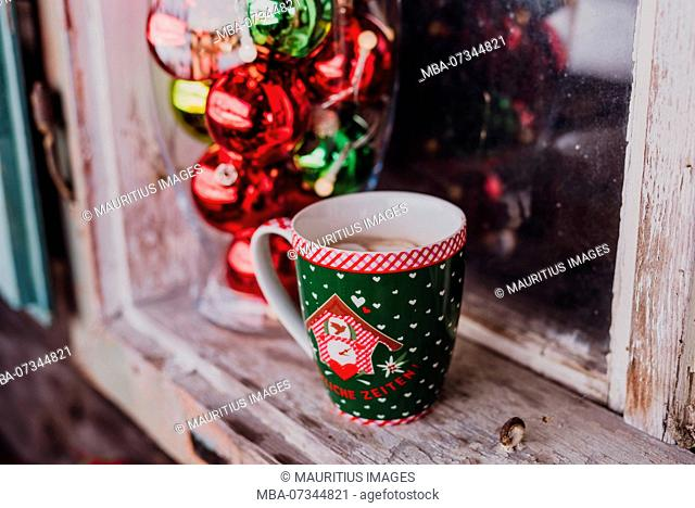 Windowsill, decoration, glass vase filled with christmas balls and a coffee cup