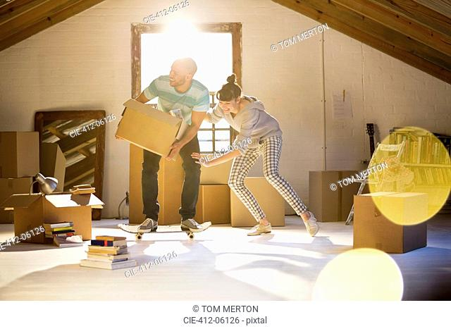 Couple unpacking boxes in attic