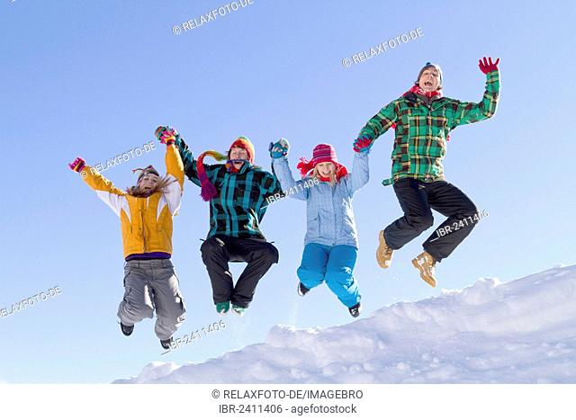 Four young people wearing colourful winter clothes jumping over a snow-covered ridge, Flachau, Salzburg, Austria, Europe