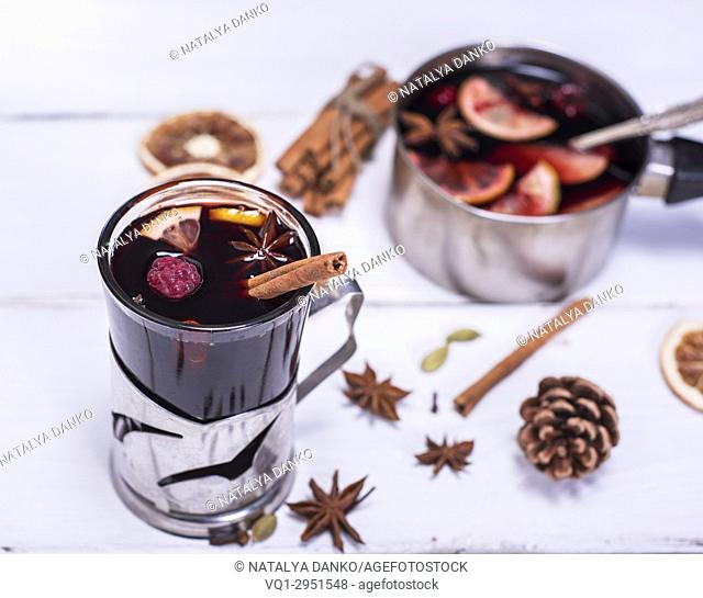 mulled wine in a glass with an iron cup holder on a white wooden background, top view