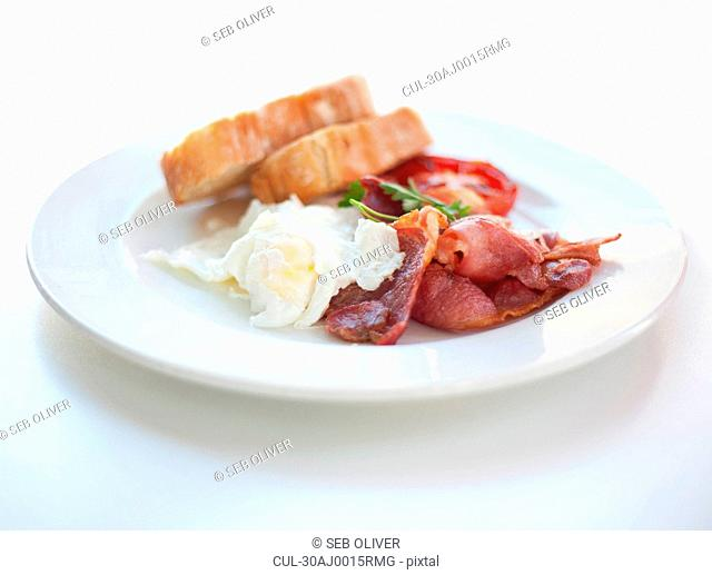 Plate of bacon, eggs and tomatoes