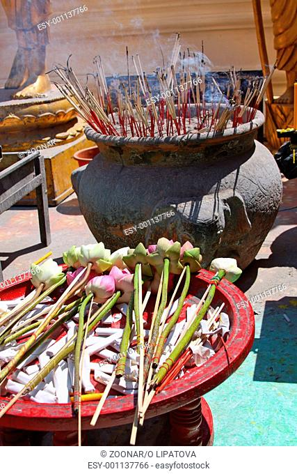 Offering in a Buddhist temple - lotus flowers and incense sticks