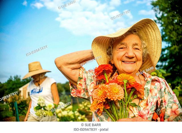 Senior woman holding onto straw hat and flowers on farm