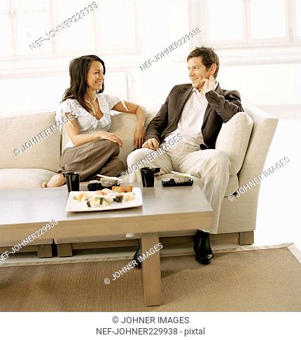 A couple sitting in the living room eating sushi