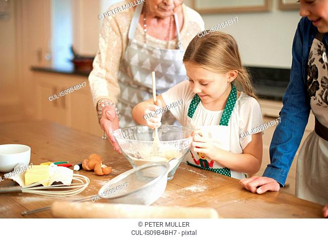 Senior woman and granddaughters stirring cookie mixture in bowl
