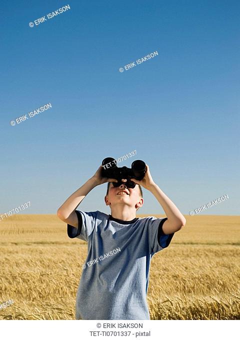 Boy in field looking through binoculars