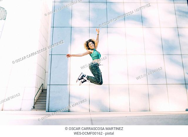 Portrait of happy young woman jumping at a building