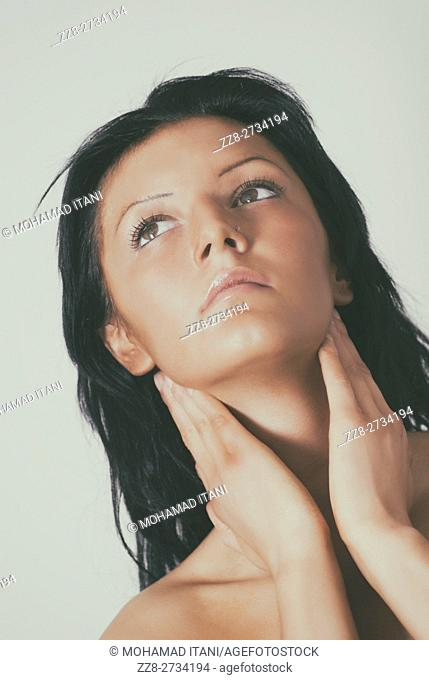 Beautiful young woman hands touching neck looking up