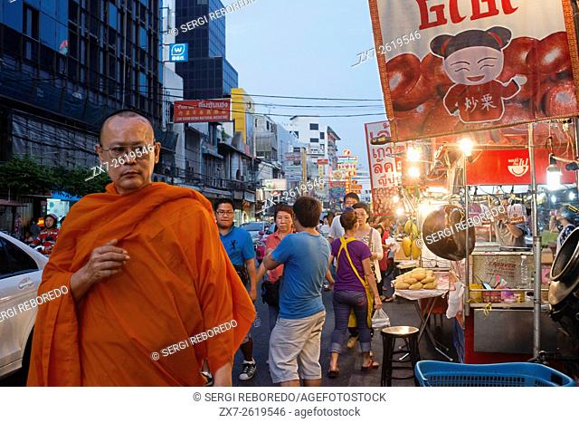 Montk in the street. View down Thanon Yaowarat road at night in central Chinatown district of Bangkok Thailand. Yaowarat and Phahurat is Bangkok's multicultural...