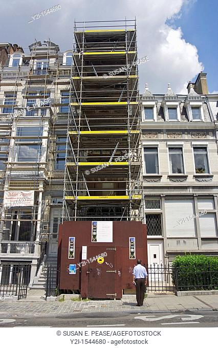 A man looks at photos of Maison St-Cyr, a historic property which in June 2009 was obscured by scaffolding while being renovated  Brussels, Belgium