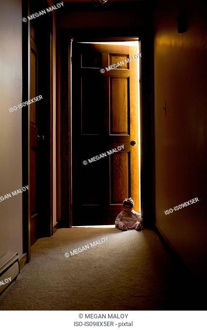 Doll sitting in doorway in hallway