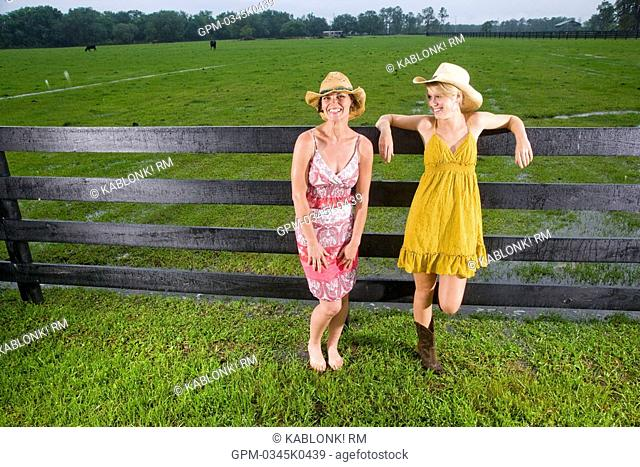 Mother and teenage daughter in dresses standing near fence on farm
