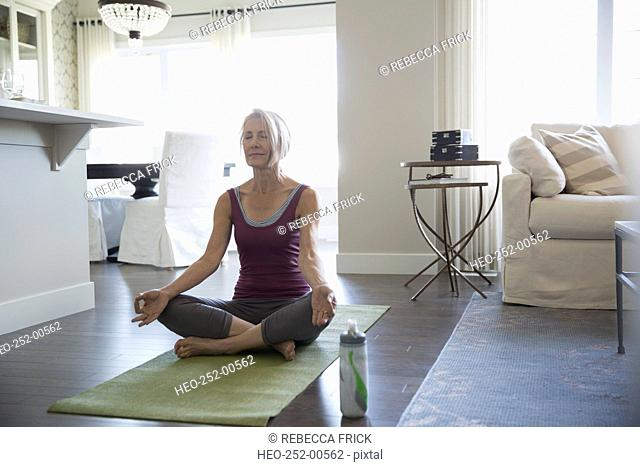 Serene senior woman meditating lotus position living room