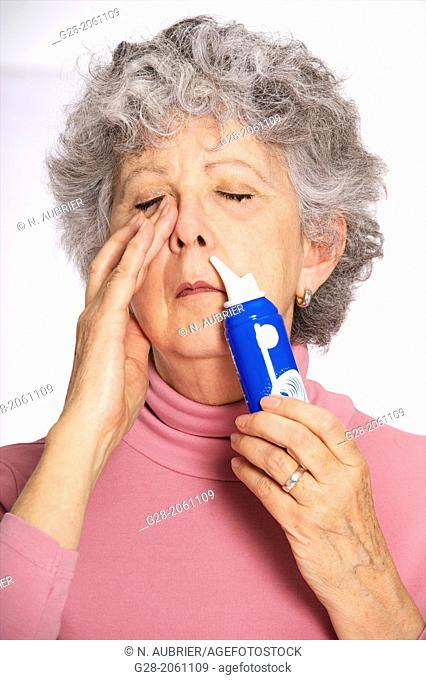 Senior woman in pink, using a blue spray of salted water for blocked nose, blocking one nostril, at home or in surgery