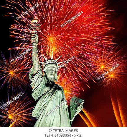 Firework display behind Statue of Liberty