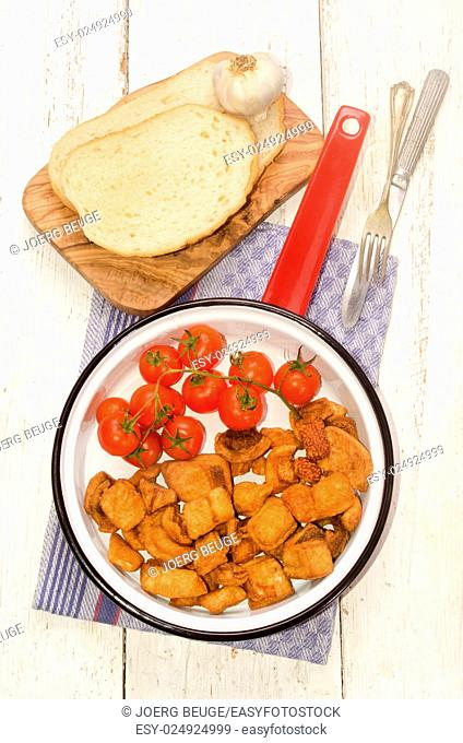crackling with cherry tomato in a red enamel pan and slice bread on wooden board