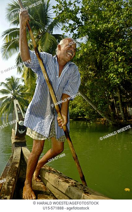 Indian boatman with a punt pole on a boat in the backwaters. Kerala, India 2005
