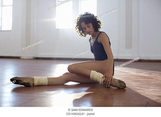 Focused, strong young female dancer stretching leg in dance studio