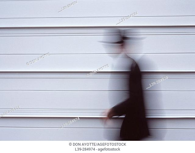Man next to building in motion