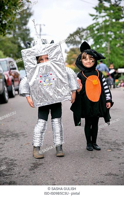 Portrait of boy in robot costume and girl in witch costume on street