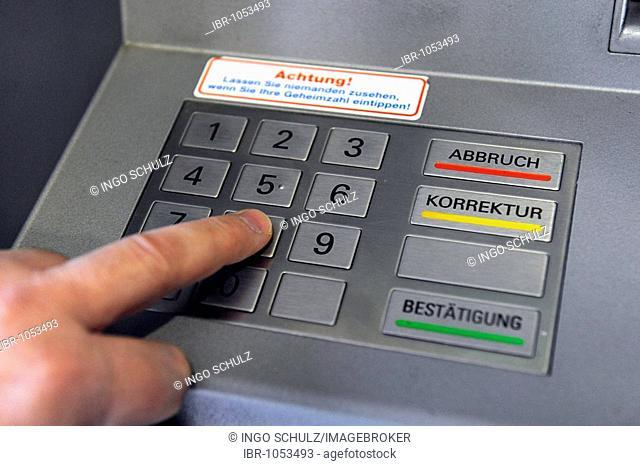 Person entering the PIN into a cash machine