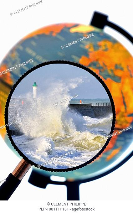 Waves crashing into jetty during storm at sea seen through magnifying glass held against illuminated terrestrial globe