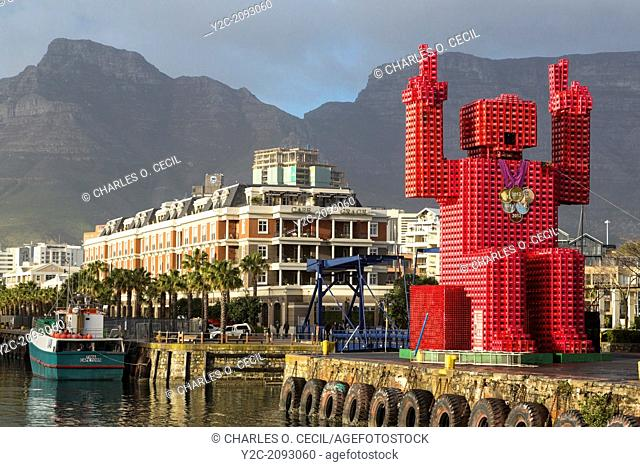 "South Africa, Cape Town. """"Lego Man"""" sculpture made of 4200 plastic Coca Cola crates. Designed by Porky Hefer. Victoria & Alfred Waterfront"