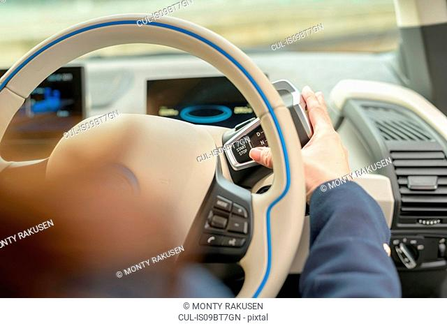 Woman pressing start button on electric car