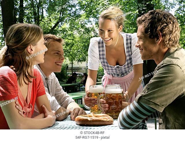 Blond woman is serving three young people with beer