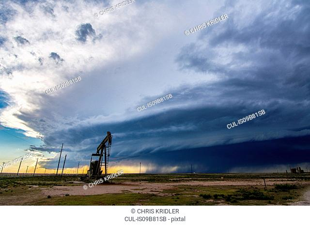 Supercell thunderstorm looms behind oil pumpjack over New Mexico desert landscape, USA