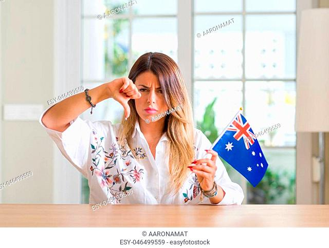 Young woman at home holding flag of Australia with angry face, negative sign showing dislike with thumbs down, rejection concept
